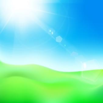 Colina verde sob o céu azul com sol.