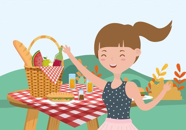 Comida de mesa mulher feliz no prado de piquenique de cesta