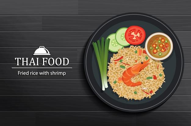 Comida tailandesa no prato na vista superior de mesa de madeira preta