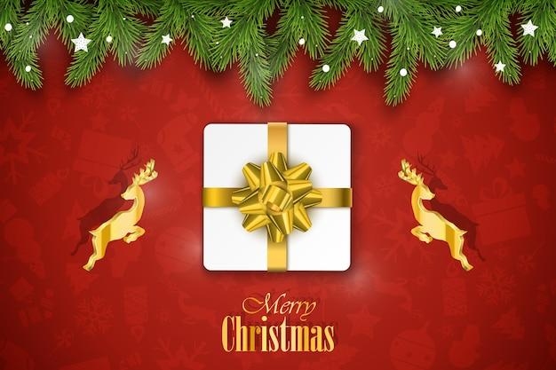 Composição de natal. desejos de férias em fundo vermelho com ramos de abeto, presente e veados dourados.