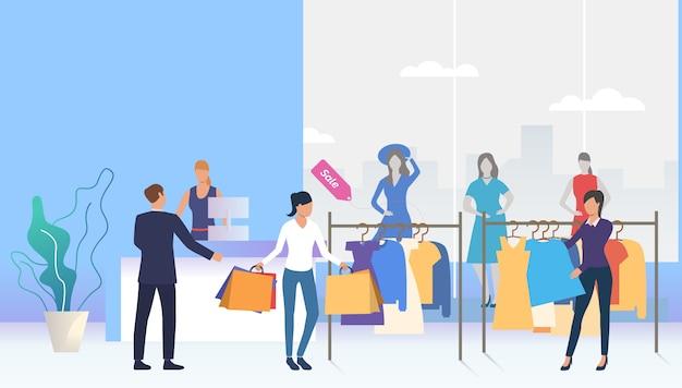 Compradores escolhendo e comprando roupas na loja