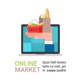 Compras na mercearia on-line e entrega de comida com a mão segurando o saco cheio de produtos de computador portátil
