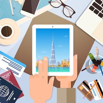 Computador da tabuleta da posse da mão com panorama do skyline de dubai, local de trabalho do viajante com ângulo superior v dos passaportes