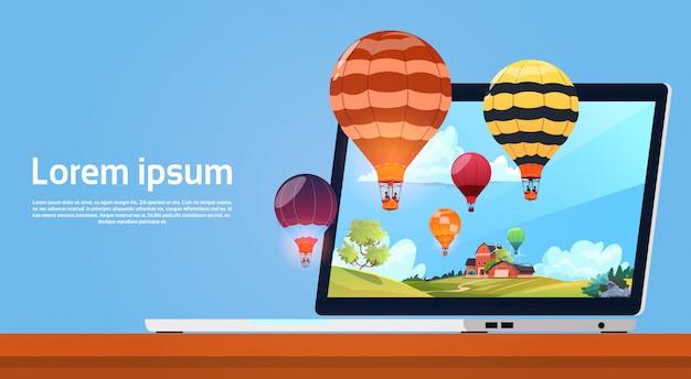 Computador portátil moderno com balões de ar colorido voando no céu