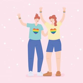 Comunidade lgbtq, mulheres jovens segurando um coração de arco-íris em camisetas, discriminação sexual em desfile gay