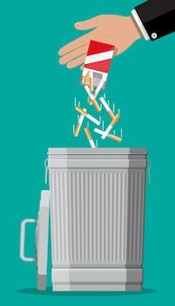 Conceito de abuso de tabaco. mão, colocando o pacote de cigarros na lixeira. proibido fumar. rejeição, proposta de fumaça. ilustração vetorial em estilo simples.