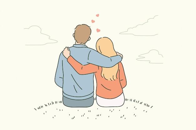 Conceito de amor, namoro, romance e sentimentos. jovem casal apaixonado, sentado de costas, abraçando-se, olhando para o horizonte, sentindo-se apaixonado.