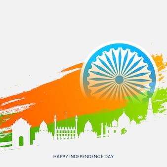 Conceito de feliz dia da independência com roda de ashoka, açafrão e efeito de pincel verde no fundo do famoso monumento de silhueta branca.