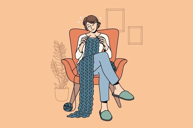 Conceito de hobbies de tricô e casa. jovem sorridente personagem de desenho animado sentada em casa na poltrona tricotando cachecol com lã, aproveitando o hobby.