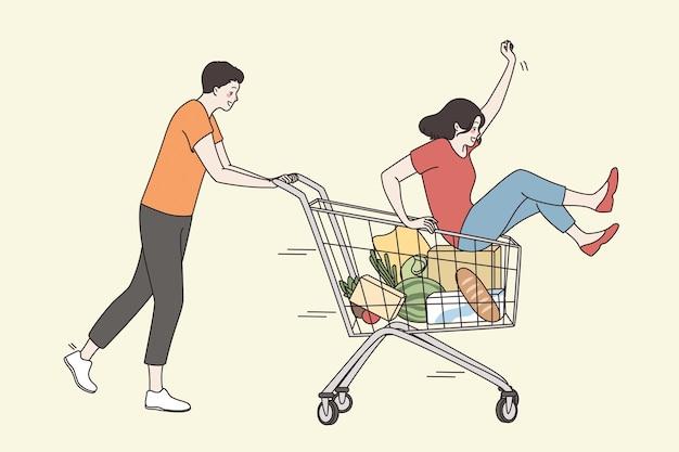 Conceito de lazer, férias e diversão. personagens de desenhos animados de jovem casal feliz brincando e se divertindo juntos no carrinho do supermercado, sentindo-se lúdico e animado.