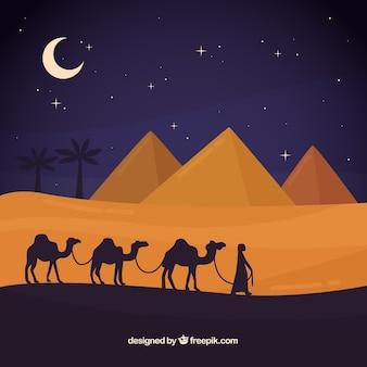 Conceito de paisagem de noite do egito com pirâmides e caravana