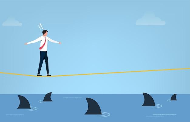 Conceito de risco empresarial. empresário andando na corda bamba com medo de tubarões.