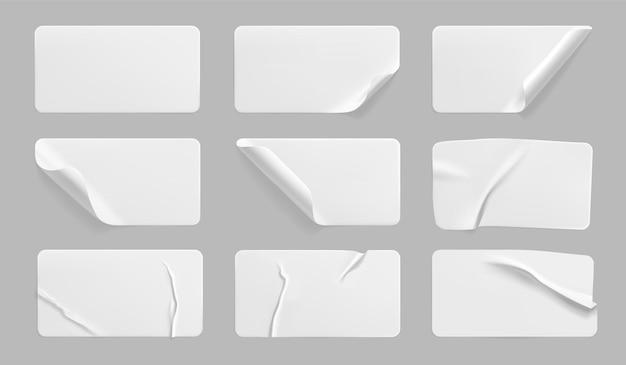 Conjunto de adesivos brancos colados amassados com cantos enrolados.