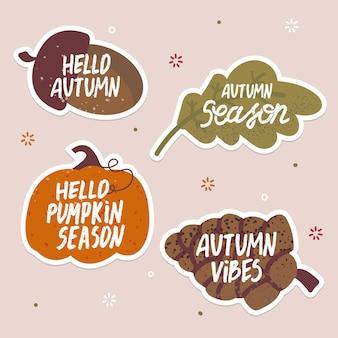 Conjunto de adesivos de outono bonitos com bolota, cone, abóbora, texto escrito à mão em folha de carvalho.
