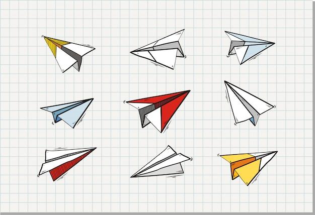 Conjunto de avião de papel origami na folha de caderno