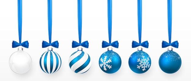 Conjunto de bola de natal transparente e azul com efeito neve e arco azul. bola de vidro de natal em fundo branco. molde da decoração do feriado.