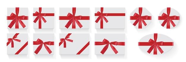 Conjunto de caixas brancas com um grande laço vermelho de presente em um fundo branco