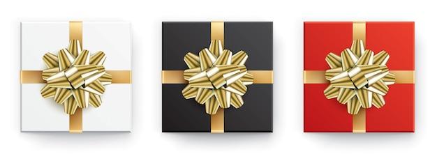 Conjunto de caixas de presente brancas, pretas e vermelhas com fitas douradas, isoladas em um fundo branco.