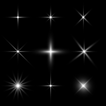 Conjunto de efeitos de luz das estrelas no preto.