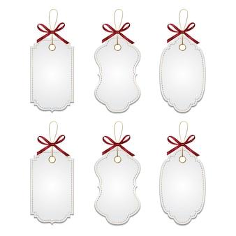 Conjunto de etiquetas brancas elegantes e realistas com laços vermelhos e elementos dourados