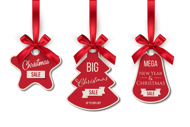 Conjunto de etiquetas de venda de natal. grandes descontos nas férias de inverno. árvore do abeto, sino, etiquetas de formas de estrela penduradas em fitas vermelhas isoladas.