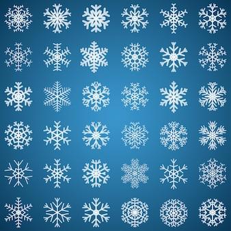 Conjunto de flocos de neve brancos de várias formas em fundo azul