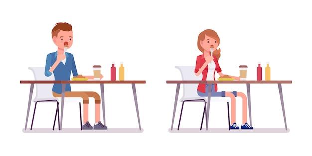 Conjunto de masculino e feminino milenar, sentado almoçando