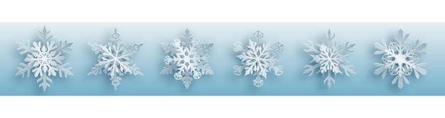 Conjunto de natal de flocos de neve de papel branco complexo com sombras suaves sobre fundo azul claro