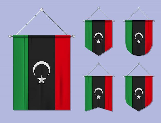 Conjunto de pendurar bandeiras líbia com textura têxtil. formas de diversidade do país de bandeira nacional. galhardete de modelo vertical
