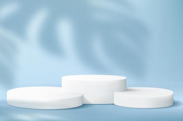 Conjunto de pódios cilíndricos para demonstração de produtos sobre fundo azul com a sombra de uma monstera.