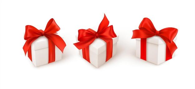 Conjunto de três caixas de presente branca com laço de fita de seda vermelha, isolado no fundo branco.