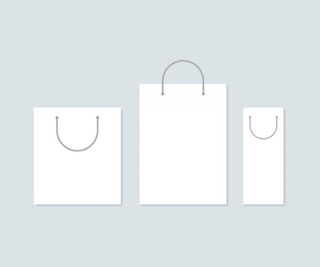 Conjunto de três sacos de compras de papel branco.