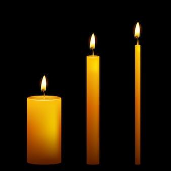 Conjunto de três velas em fundo escuro.