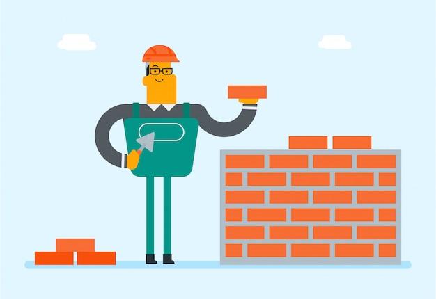 Construtor branco caucasiano que constrói uma parede de tijolo.
