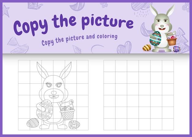 Copie a imagem do jogo infantil e a página para colorir com o tema páscoa com um coelho fofo segurando o ovo de balde e o ovo de páscoa
