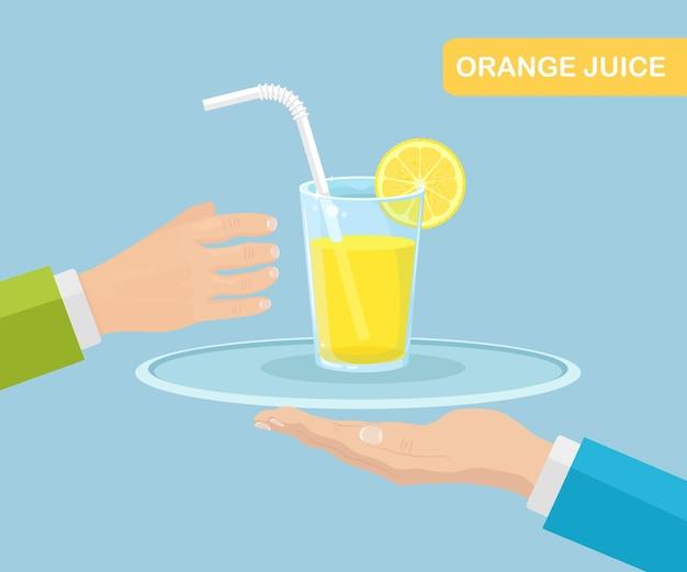 Copo de suco de laranja com canudo e uma fatia de frutas cítricas na bandeja. garçom serve bebidas