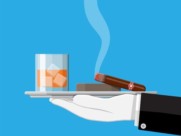 Copo de whisky com charuto e cinzeiro na mão