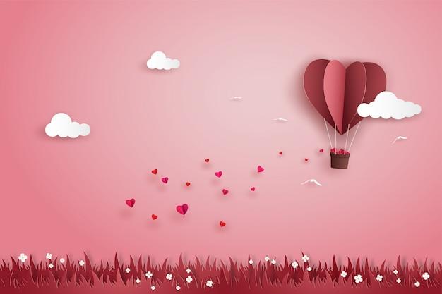 Coração de balão de origami voando com muitos mini corações no céu sobre o prado no dia dos namorados.
