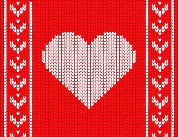 Coração de malha sobre um fundo vermelho. camisola aconchegante.