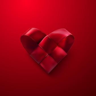 Coração tecido de tecido vermelho sobre fundo vermelho
