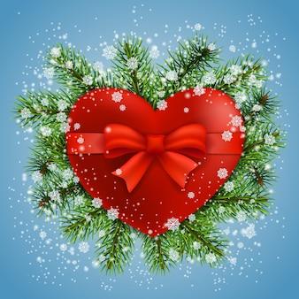 Coração vermelho em ramos de abeto com neve sobre fundo azul. cartão de felicitações.