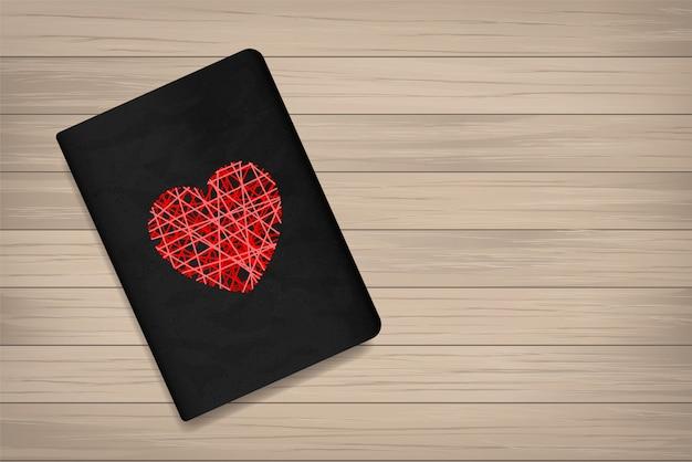 Coração vermelho na capa do livro com fundo de madeira.