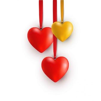 Corações 3d dourados e vermelhos com fitas.