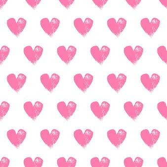 Corações cor-de-rosa pintados no teste padrão sem emenda branco.