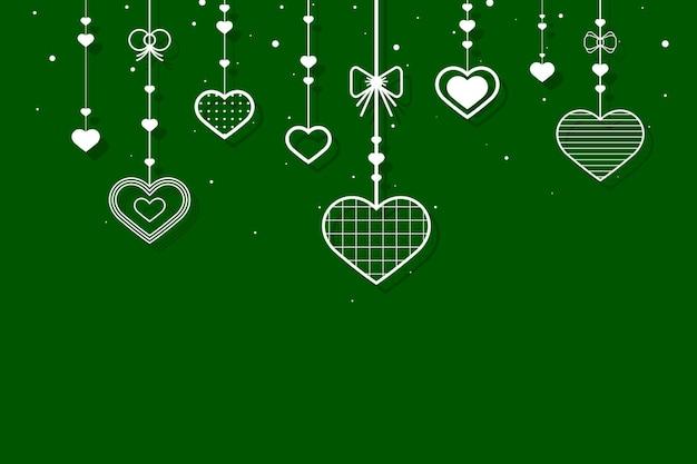 Corações pendurados em fundo verde