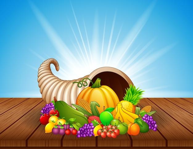 Cornucópia de outono com legumes e frutas na mesa de madeira