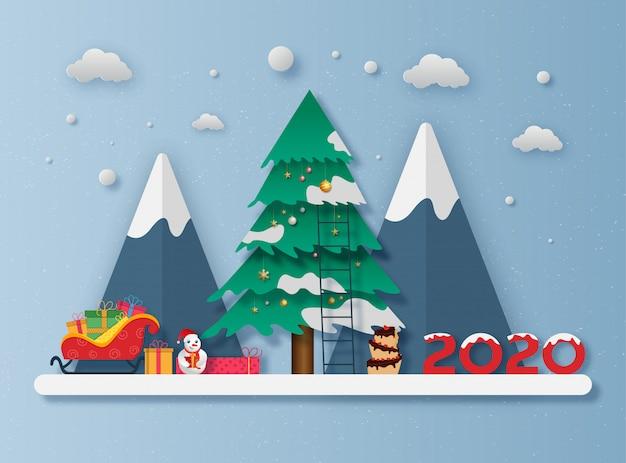 Corte de papel estilo árvore de natal com montanhas, boneco de neve, caixa de presente no trenó e bolo para a celebração do ano 2020