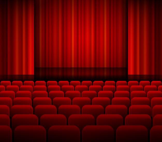 Cortinas abertas de teatro vermelho com luz e assentos.
