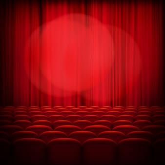 Cortinas vermelhas de teatro fechadas com holofotes e assentos.