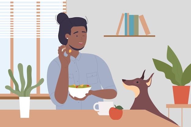 Cozinhando o homem na cozinha com um cachorro feliz, o dono do animal, sentado à mesa, segurando comida de cachorro